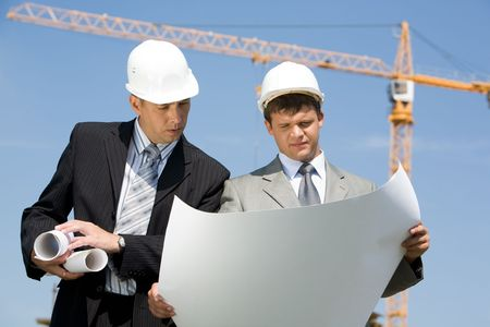Portrait of two confident foremen looking at project on the background of sky and crane  Stock Photo - 4920743