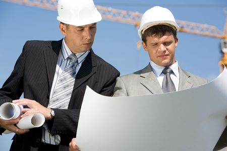 Portrait of two architects looking at project on construction site  photo
