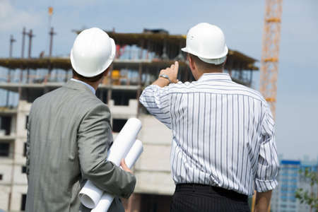 Rear shot of boss pointing at construction with worker near by  photo