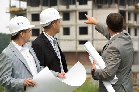 Bild von drei Arbeitnehmern suchen Bau während der Diskussion der architektonischen Projekt