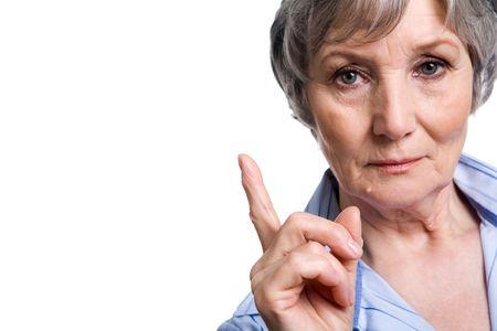 Photo of elderly female with her forefinger pointed upwards on white background Stock Photo - 4920763