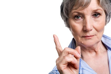 serious woman: Photo of elderly female with her forefinger pointed upwards on white background Stock Photo