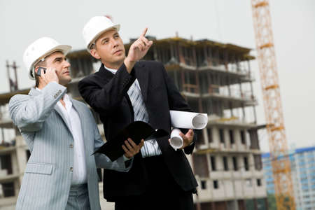 Photo of serious employee pointing at something with calling foreman standing near by photo
