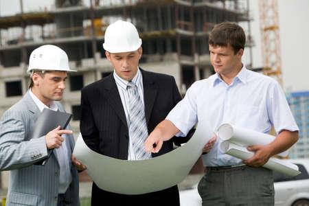 arquitecto: Retrato de tres constructores permanente en obras de construcci�n y discusi�n de nuevos proyectos en manos de uno de ellos