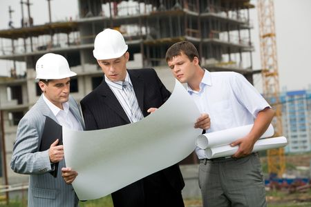 construction companies: Portrait of three builders looking at new project and discussing it outside Stock Photo