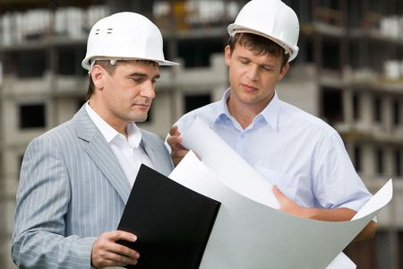 Portrait of confident colleagues looking at new construction plan and brainstorming photo