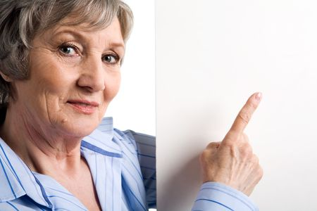 Image of elderly female pointing at blank copyspace and looking at camera Stock Photo - 4920748