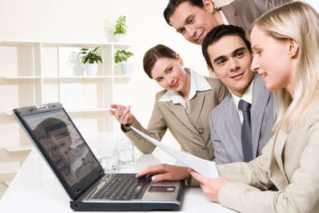 workteam: Portrait of friendly workteam looking at confident businesswoman with document in hand typing on laptop