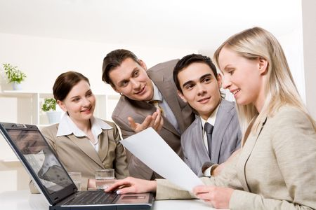 workteam: Portrait of friendly workteam looking at confident businesswoman with document in hand and sharing their ideas Stock Photo