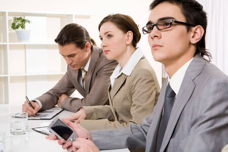 attentively: Photo of confident businesspeople listening attentively to speech at conference Stock Photo