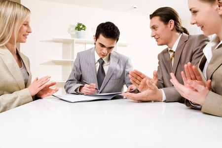 Photo of successful businessman signing contract with promising company while colleagues applauding photo
