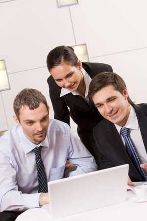 Portrait of executive employees looking at laptop monitor with smiles and thinking about new project Stock Photo - 4938622