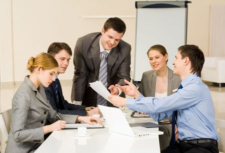 portrait of confident man showing document to co workers and stock