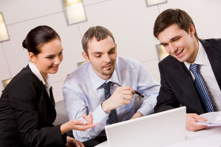 Portrait of executive employees looking at laptop monitor and discussing new project during meeting Stock Photo - 4938510