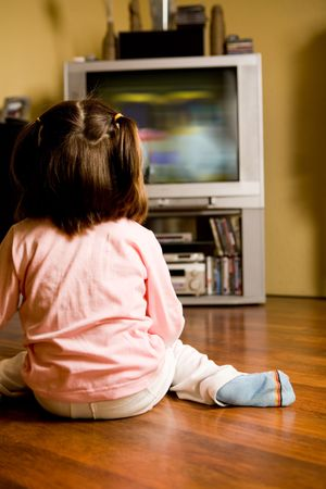 backwards: Rear view of little girl sitting on the floor and watching cartoons on TV at home