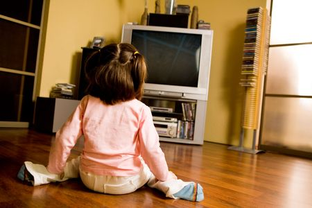 tv screen: Rear view of little girl sitting on the floor and watching TV in living-room