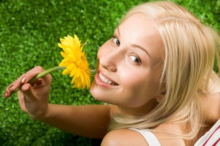 Close-up of cheerful young female with yellow beautiful flower in hands looking at camera Stock Photo - 4941356