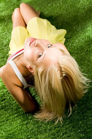 Photo of young blond female lying on green grassland and looking at camera Stock Photo - 4941355