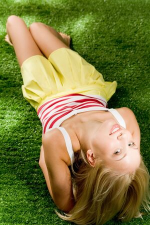 Photo of happy blond female lying on green grassland and looking at camera Stock Photo - 4941351