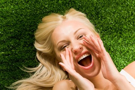 Photo of shouting female lying on green grass and looking at camera Stock Photo - 4941349