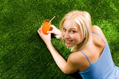 Photo of happy blond female lying on green grass with glass of juice and looking at camera Stock Photo - 4941353