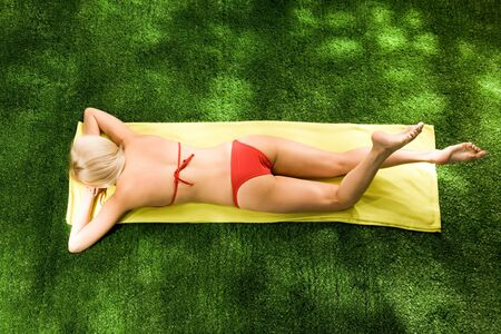 Above view of beautiful female in red swimsuit lying on belly and sunbathing on sunny day photo