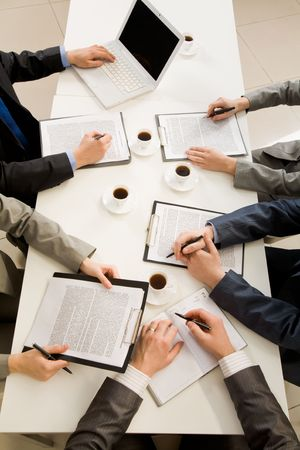 place to learn: Image of business people hands with ballpoints writing on papers while planning work