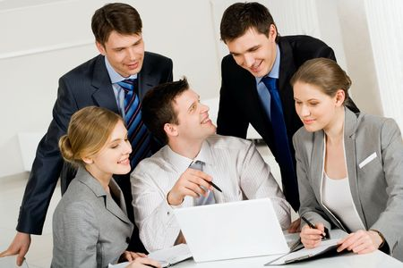 workteam: Portrait of friendly workteam looking at laptop monitor while confident man sharing his idea with co-worker Stock Photo