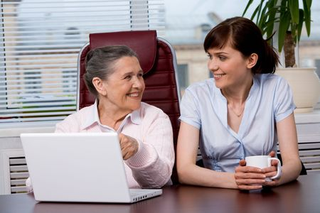 Portrait of elderly woman consulting her pretty granddaughter what to type photo