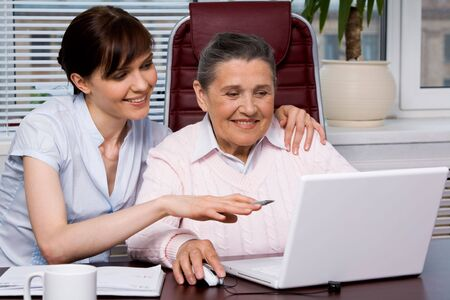 Portrait of young girl pointing at laptop monitor while embracing her grandmother photo