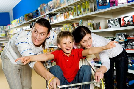 Image of cute kid in handcart with his arms stretched surrounded by parents photo