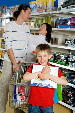Portrait of joyful lad holding box in hands with his parents at background in toy department photo