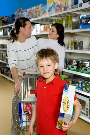 Portrait of smiling lad with box looking at camera on background of his parents in the mall photo