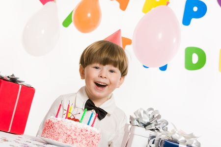 Portrait of happy boy looking at camera and laughing on birthday party photo