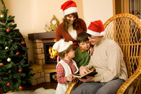 Portrait of smiling man with book in hand sitting in rocking-chair and looking at his little sons standing near by Stock Photo - 6140562