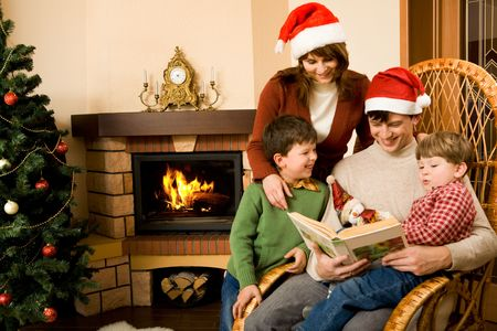 Portrait of friendly family looking into interesting book on Christmas day photo