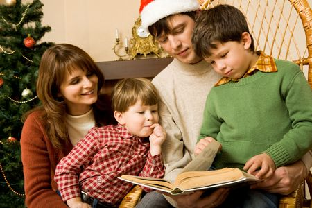 Portrait of friendly family looking into interesting book on Christmas day Stock Photo - 6140604