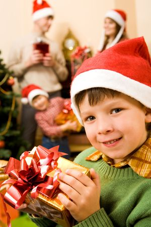 Image of glad boy with Christmas present on background of his brother and parents photo