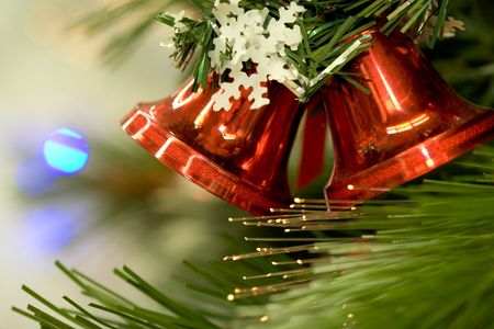 feliz: Close-up of red toy bells hanging on green spruce branch decorated with paper snowflake