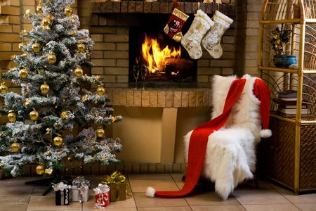 Christmas room with fireplace, chair, presents under decorated fir tree and toys in it photo