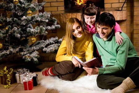 Portrait of cheerful family sitting on white fur reading old book with decorated fir tree near by photo