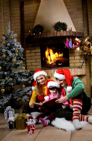 Portrait of family reading book by fireplace on Christmas evening Stock Photo - 6140606