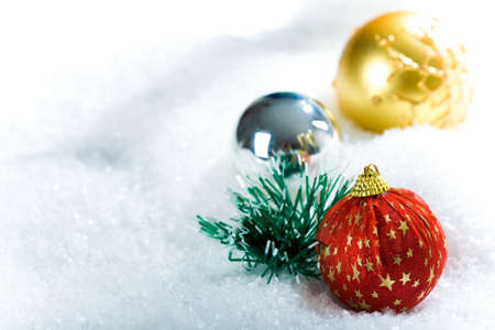 christmastide: Close-up of Christmas ball of red color decorated with golden stars in snow