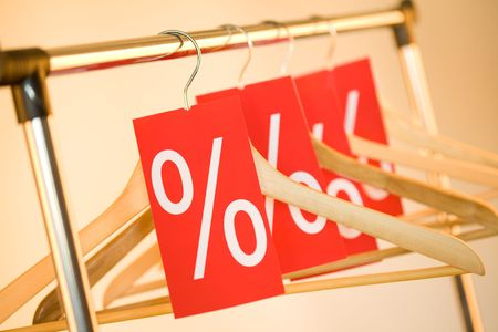 Image of several wooden hangers with red labels showing discount on them photo