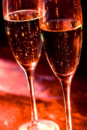 Close-up of two flutes of champagne over dark lit background photo