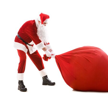 xmass: Portrait of happy Santa carrying heavy big red sack with presents Stock Photo