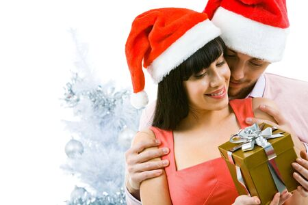 Portrait of happy woman looking at giftbox in her hands while being embraced by loving man photo