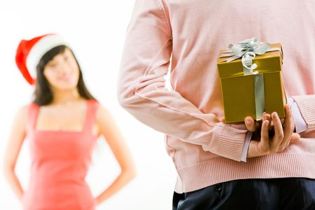 intrigued: Rear view of man holding giftbox in hand on background of intrigued female