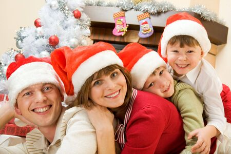 Portrait of happy family wearing Santa caps and looking at camera with smiles photo