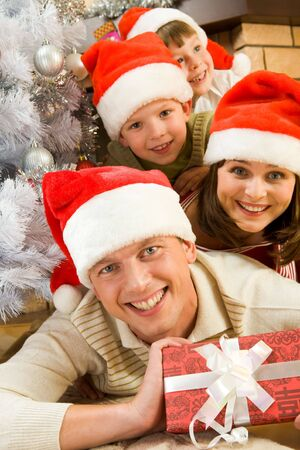 Portrait of happy man in Santa cap holding giftbox with his family on background photo